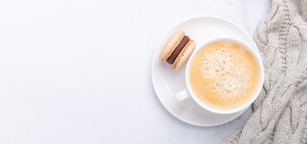 돌 배경에 니트 스카프, 커피, 초콜릿 마카롱이 있는 가로 배너. 아늑한 가을 구성입니다. 평면도, 평면도 - 이미지