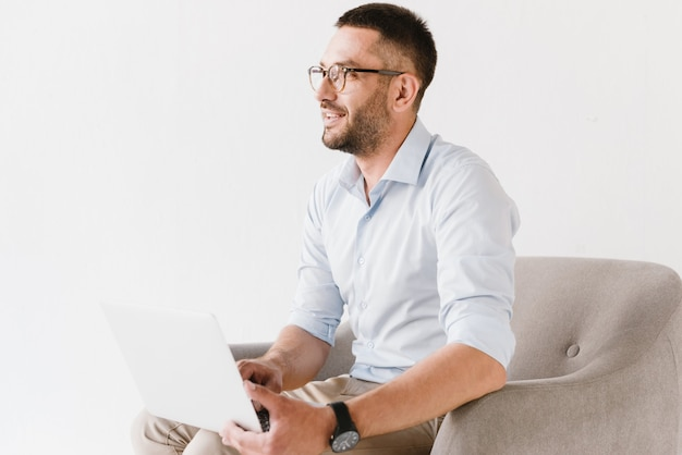 肘掛け椅子に座って、白で隔離され、ラップトップに取り組んでスタイリッシュなフォーマルな服を着ている水平ひげを生やした白人男