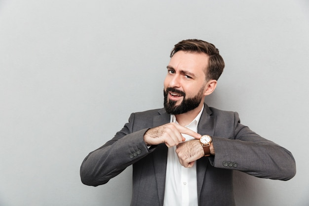 Horizontal bearded man pointing at his wrist watch, posing isolated over gray