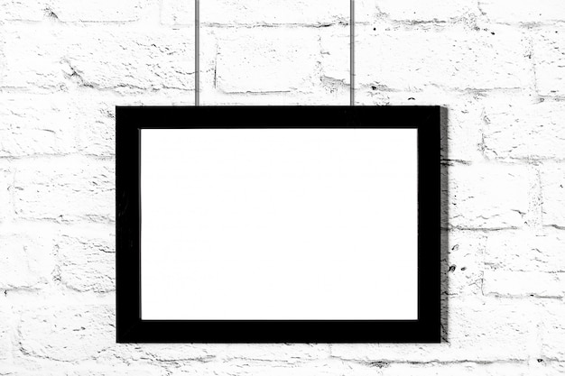 Horizontal black photo frame hanging on brick wall. mockup with copy space