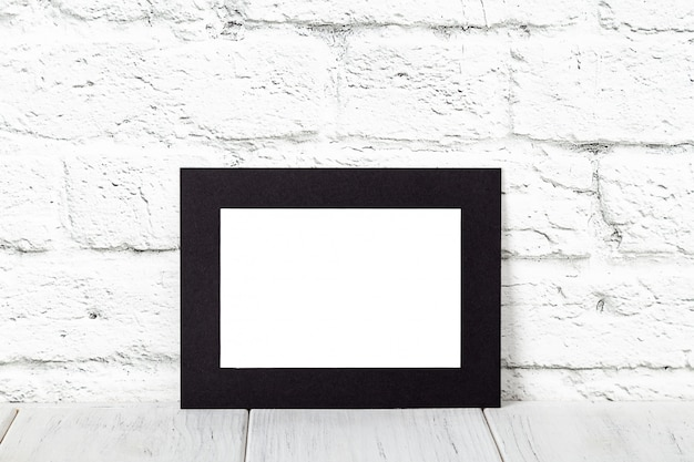 Horizontal black photo frame on wooden table. mockup with copy space