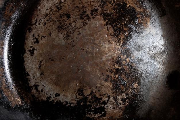 Горизонтальное дно сильно используемой текстуры железной сковороды со смазкой