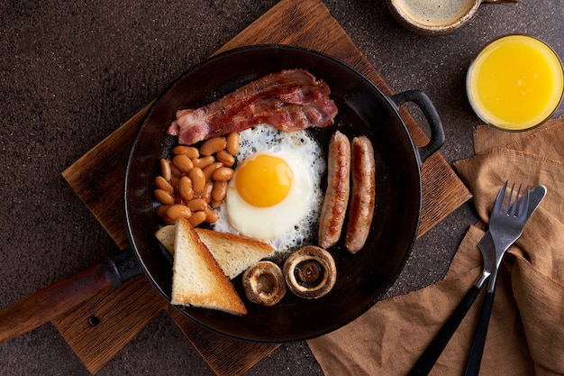 Horizontal of classic pan fried delicious fatty rustic english breakfast on wooden table