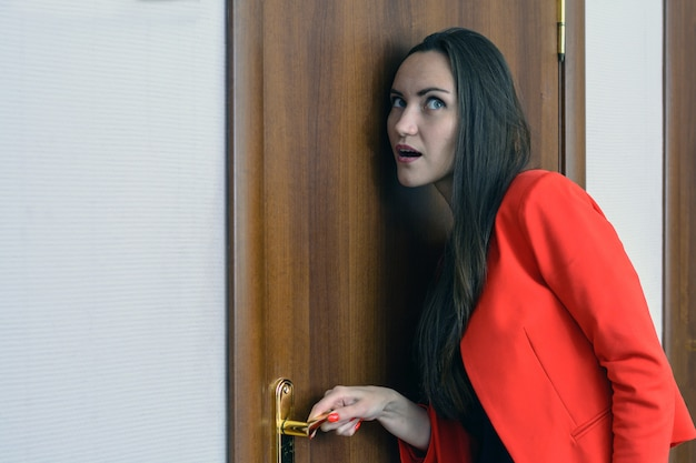 Horizontal close-up portrait of a woman in a red suit eavesdropping, spying on the door of the boss