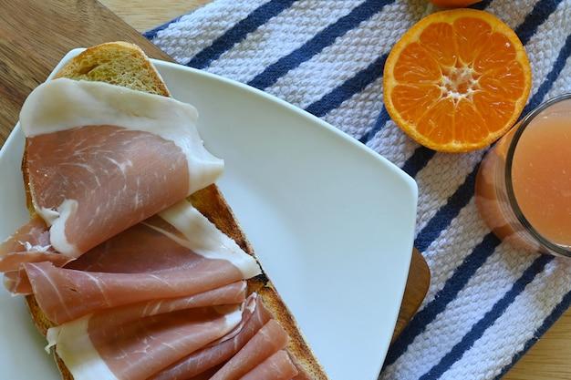 ハムとオレンジジュースのトースト、縞模様の生地の背景の水平方向のクローズアップ