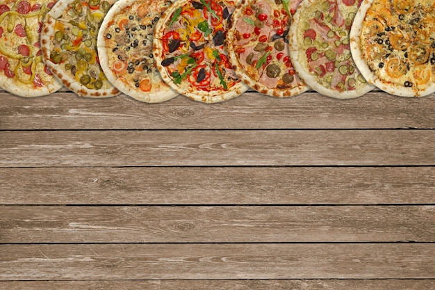 Horizontal collage of different baked pizzas on dark wooden table. top view.