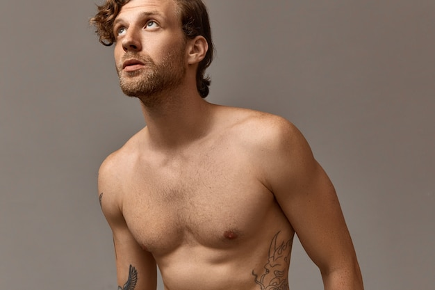 Horizontal cropped picture of attractive male with athletic torso posing without shirt. handsome unshaven tattooed caucasian male with stylish haircut and naked chest looking upwards