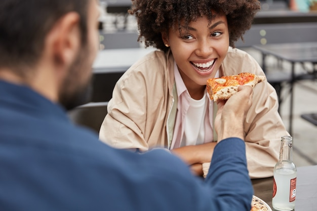 Horizontal cropped view of cheerful black woman with afro hairstyle eats delicious italian pizza from boyfriends hands