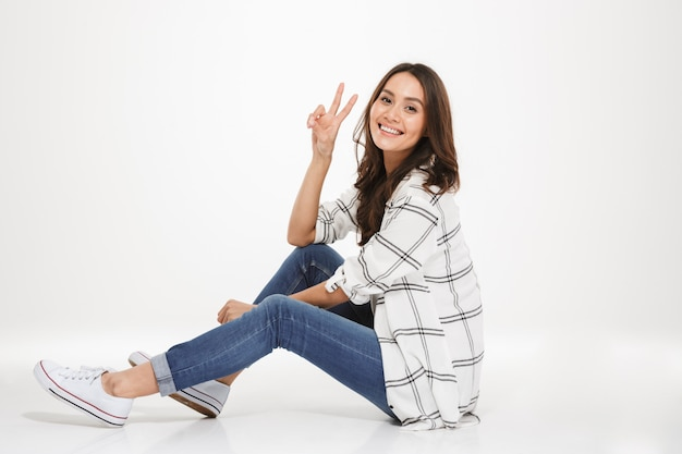 Horizontal cute young woman with brown hair sitting in profile on the floor and showing victory sign, isolated over white wall