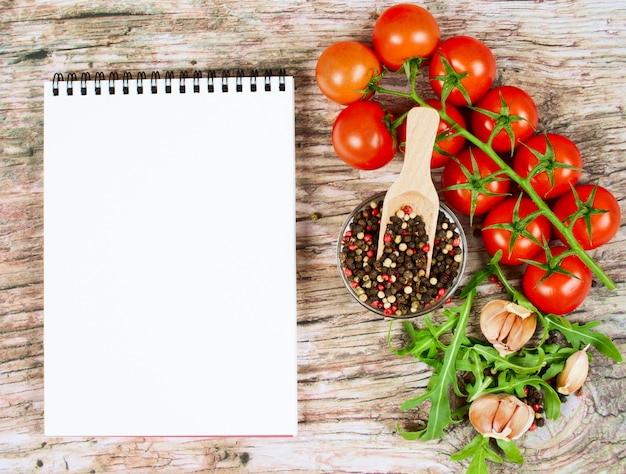 Horizontal food banner with cherry tomatoes, arugula, garlic, peppercorns and notebook.
