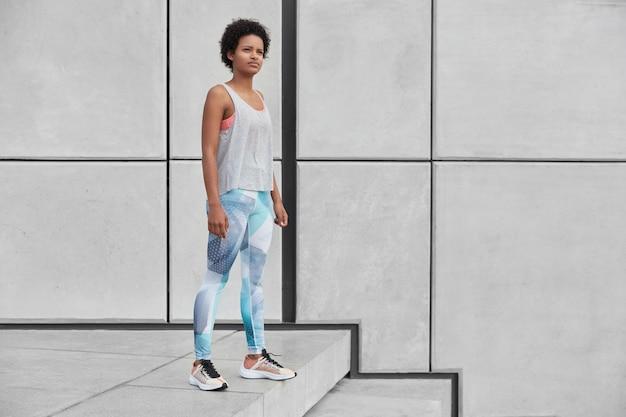 Colpo orizzontale a figura intera di un istruttore di fitness femminile premuroso auto-determinato si trova sulle scale, indossa abiti sportivi, farà un allenamento di ginnastica con il tirocinante, spazio libero da parte per il tuo testo