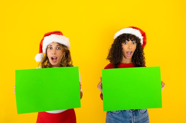 Horizontal funny christmas banner with two mixed race women with mouth and eyes wide open in surprised expression holding green cart for copy space adv message in chroma key in yellow background