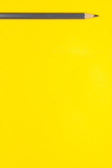 Horizontal gray sharp wooden pencil on a bright yellow background, isolated, copy space, mock up