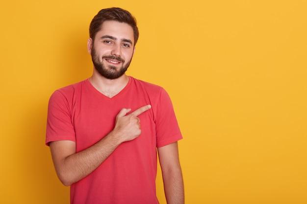 Il maschio con la barba lunga bello orizzontale, vestito in maglietta rossa casuale, indicando da parte il dito indice, mostra lo spazio della copia per la vostra pubblicità o il testo di promozione.