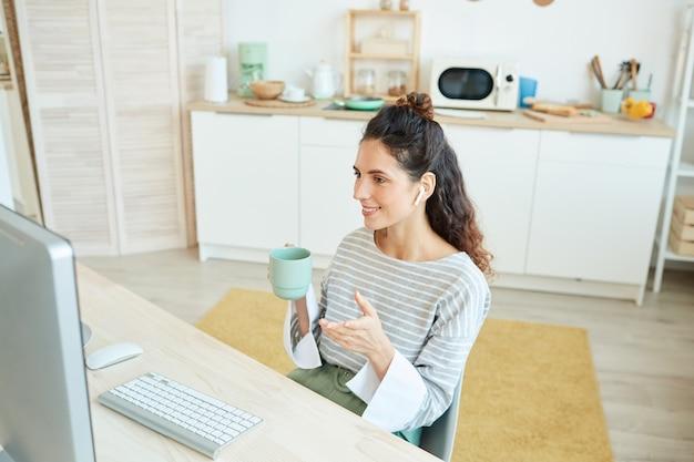 집에서 데스크톱 컴퓨터와 무선 이어폰을 사용하여 온라인 회의에 참여하는 매력적인 젊은 관리자의 수평 높은 각도 샷