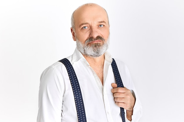 Horizontal image of attractive serious bearded retired male with bald head and wrinkled face posing isolated against blank wall background, pulling one strap of suspenders, having confident look