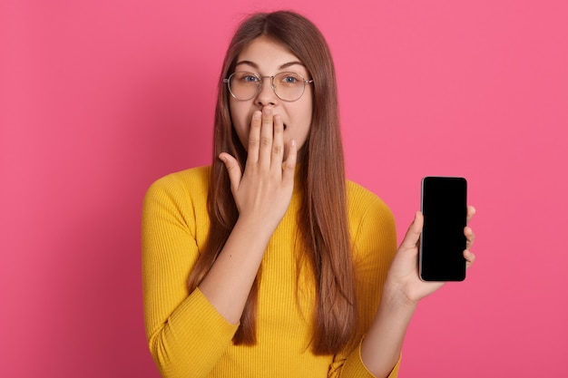 Horizontal image of beautiful young lady standing isolated over pink wall in studio, covering mouth with hand, holding smartphone, wearing eyeglasses and yellow sweatshirt. emotions concept.