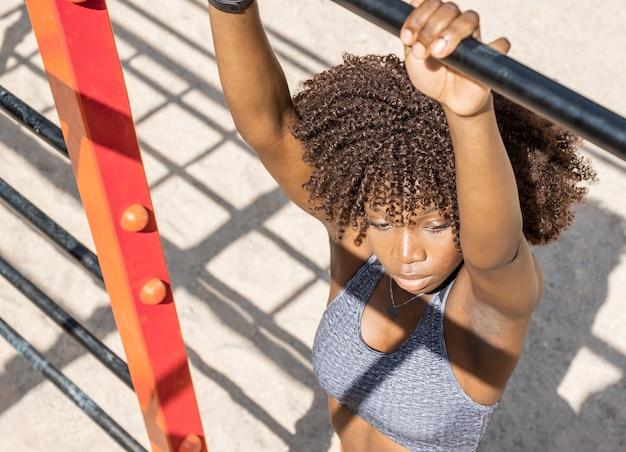 단단한 자연 채광이 있는 검은색 미용실에서 회색 상단을 움켜쥐고 있는 아프로 머리 어린 흑인 소녀의 위에서 수평 이미지