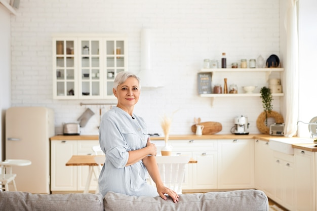 Horizontal image of gorgeous joyful elderly sixty year old housewife having rest after cleaning all rooms, having cheerful facial expression, standing in living room with kitchen in
