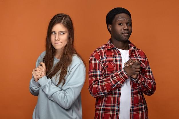L'immagine orizzontale della coppia interrazziale si tirano trucchi a vicenda, in posa isolata contro il muro arancione vuoto, guardando sospettoso, pianificazione trucco o scherzo, strofinando le mani