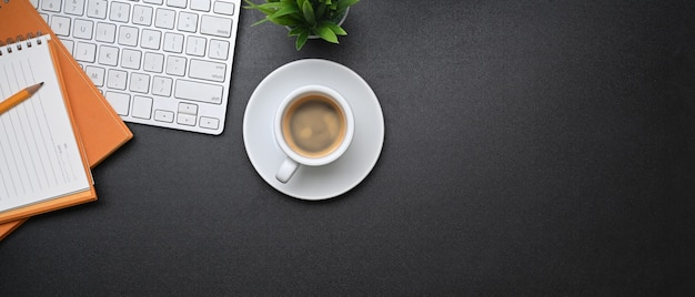 Horizontal image of modern workplace with coffee cup, notebook, wireless keyboard and copy space on dark background.