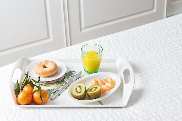 Горизонтальное изображение подноса с пончиком на завтрак с мандарином, киви и апельсиновым соком на белой кровати