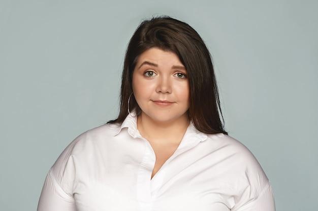 白いフォーマルなシャツと丸いイヤリングを身に着けている魅力的な若い太りすぎのプラスサイズの女性の水平方向の画像は、空白の灰色の壁でポーズをとって、心配、困惑、またはイライラした表情をしています