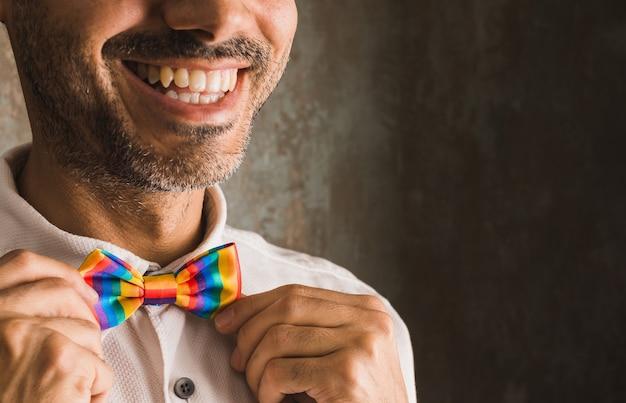 Горизонтальное изображение брюнетки с бородой, улыбающегося в белой рубашке и лгбтчи + радужном галстуке-бабочке в левой части изображения на изношенной стене, освещенной мягким боковым светом