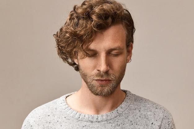 평화로운 수염 난 잘 생긴 남자의 수평 이미지는 볼륨있는 붉은 머리카락을 감고 눈을 감고 호흡에 집중하려고 노력하고 명상합니다. 마음 챙김, 균형, 조화 및 평화 개념