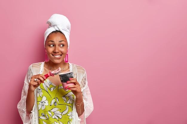 웃는 어두운 피부 아가씨의 수평 이미지는 머리, 캐주얼 복장에 수건을 착용하고 맛있는 차가운 아이스크림으로 달콤한 치아를 만족시키고 숟가락, 냉동 디저트 컵을 보유하고 분홍색 벽에 고립