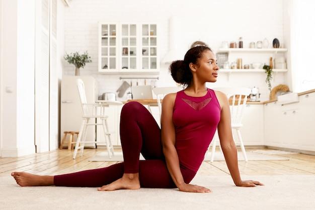 片方の膝を曲げてマットの上に座って、頭を回して、ヨガを練習しているスポーツ服を着たスポーティでスタイリッシュな若いアフリカ系アメリカ人女性の水平方向の画像。健康的なライフスタイル、幸福と活動の概念