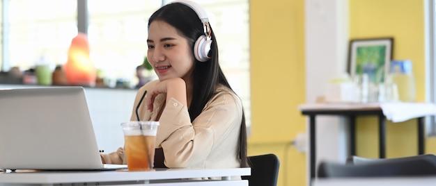 コーヒーショップに座っている間、ラップトップコンピューターを介してオンラインで学習するヘッドフォンを身に着けている学生の女の子の水平方向の画像。