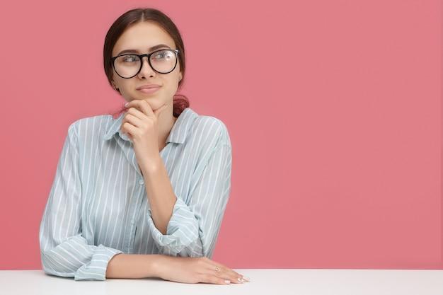 Горизонтальное изображение задумчивой красивой молодой женщины в очках, смотрящей в сторону с задумчивой мечтательной улыбкой, держащей руку за подбородок, развивающей бизнес-стратегию, имеющей множество творческих идей