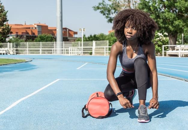 파란색 달리기 트랙에서 옆을 바라보며 신발끈을 묶고 웅크리고 있는 아프리카 머리를 가진 젊은 흑인 운동선수 소녀의 수평 이미지
