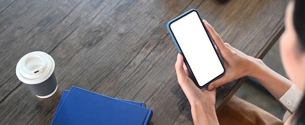 Горизонтальное изображение молодой женщины, отдыхающей в кафе и использующей смартфон
