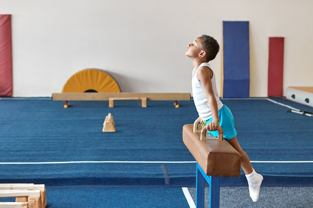 Horizontal image of skilled afro american boy gymnast preparing for artistic gymnastics competition