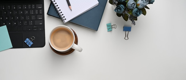 Horizontal image of white office desk with coffee cup, plant, notebook and keyboard.