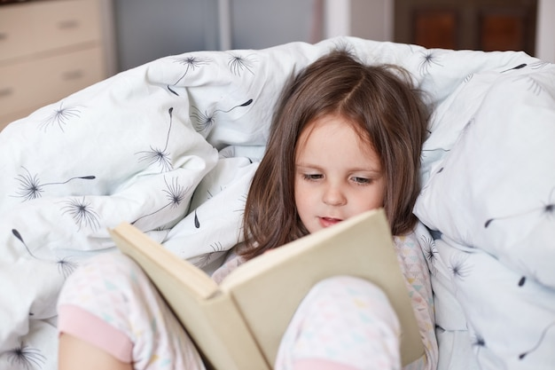 Horizontal indoor picture of curious interested busy infant spending free time alone, reading attentively, studying, lying in bedroom at blanket, wearing pajama. children and free time activities.