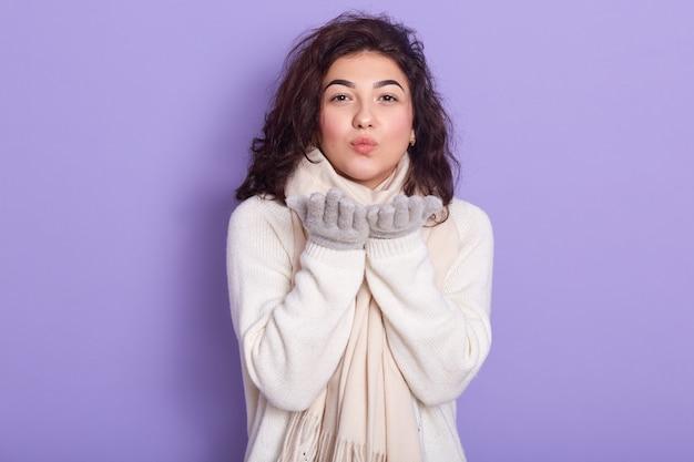 白いセーターを着て、スタジオで薄紫色の背景に分離された感情的な魅力的なブルネット立っての水平屋内ショット