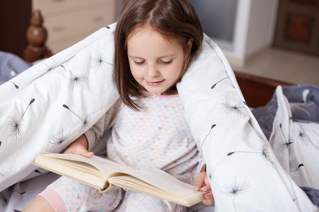Horizontal indoor shot of playful smart sweet kid holding book in both hands, looking through attentively, sitting in her bedroom under blanket, wearing pajamas.