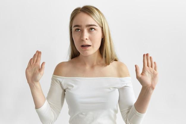 Горизонтальная раздраженная раздраженная молодая блондинка в стильной топе закатывает глаза и делает стоп-жест
