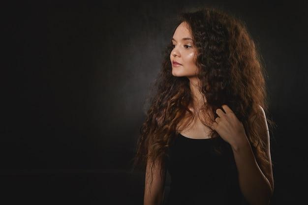 Горизонтальное изолированное изображение модели привлекательной очаровательной молодой брюнетки в черном топе с серьезными выражениями лица