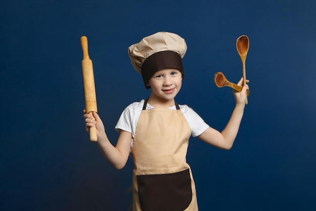 Horizontal isolated shot of cute 10 year old caucasian boy wearing apron and chef hat posing
