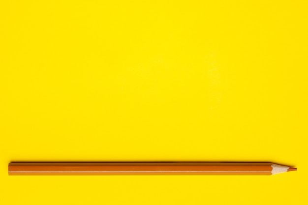 Horizontal light brown sharp wooden pencil on a bright yellow background, isolated, copy space, mock up