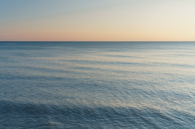 Horizontal line between sea and sky at sunset