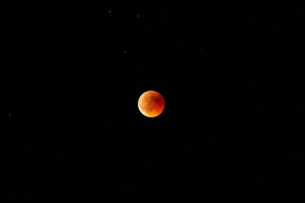 Horizontal long shot of an orange and red moon in the dark sky at night