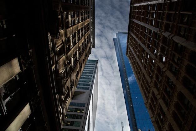 息をのむような曇り空の下で反射する高層ビルの水平ローアングルショット