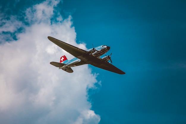 Colpo orizzontale di angolo basso di un aeroplano d'argento sotto il bello cielo nuvoloso