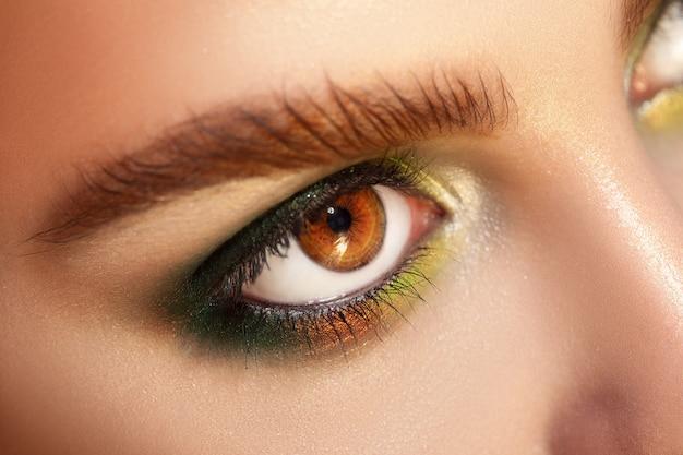 Горизонтальное макро фото карих глаз с зеленым макияжем
