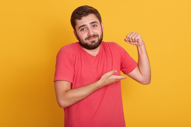 Horizontal male in sleeveless t shirt show his weak biceps muscles, young handsome unshaven man posing isolated on yellow wall, attractive guy with beard.